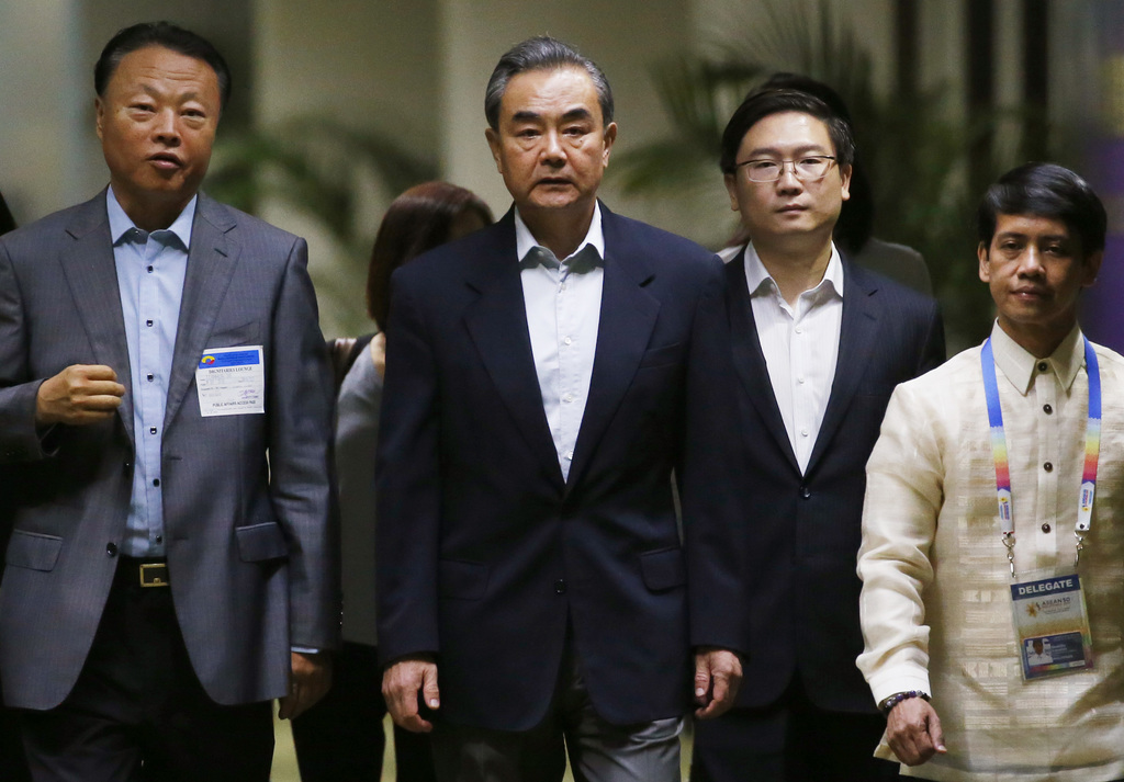 Chinese Foreign Minister Wang Yi, center, is escorted by Chinese Ambassador to the Philippines Zhao Jianhua, left, upon arrival to take part in the 50...
