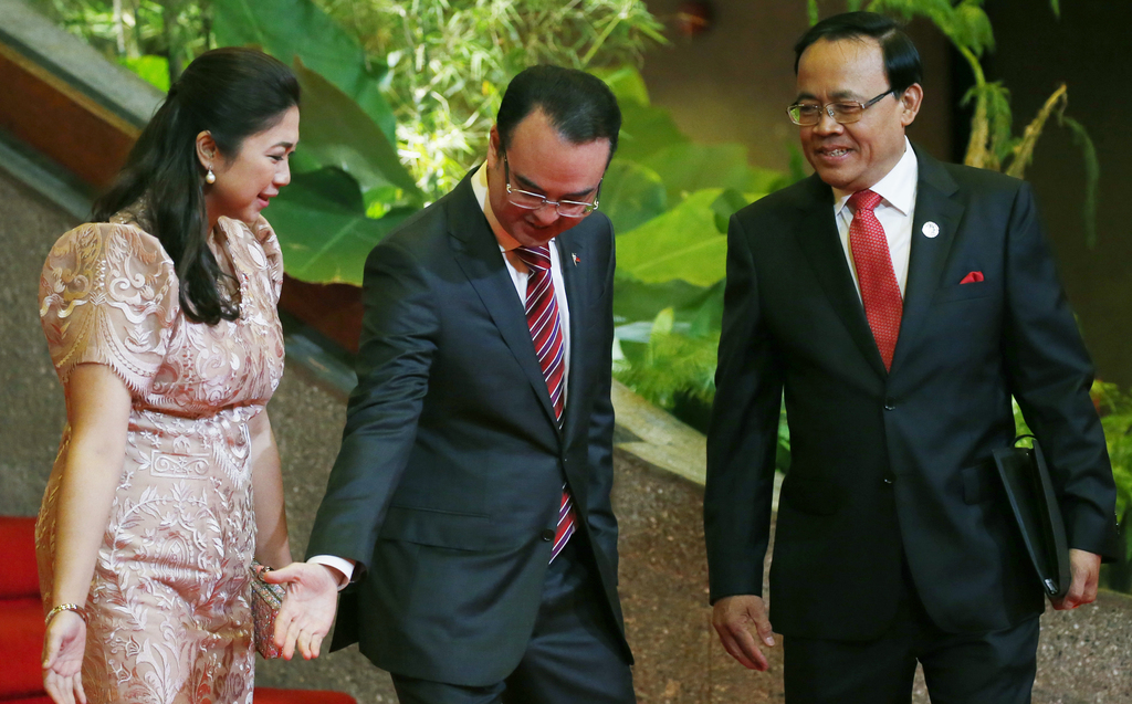 Philippine Foreign Affairs Secretary Alan Peter Cayetano, center, and his wife Lani, left, greet Myanmar's Foreign Minister Kyaw Tin during a receptio...