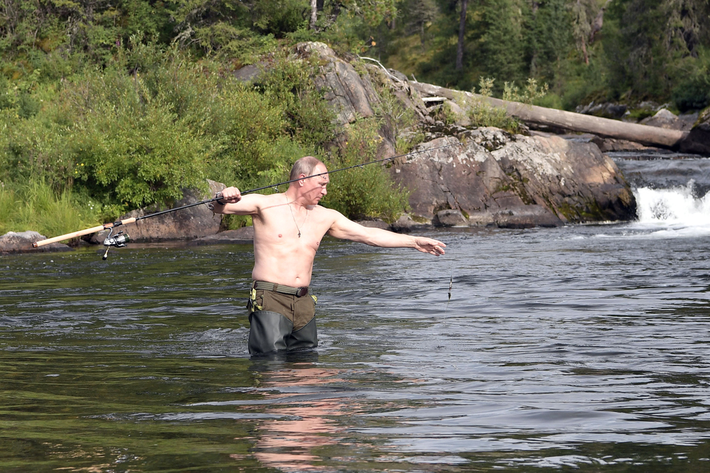 In this photo released by Kremlin press service on Saturday, Aug. 5, 2017, Russian President Vladimir Putin fishes during a mini-break in the Siberian...