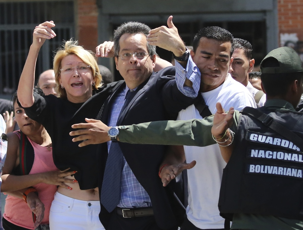 Venezuelan General Prosecutor Luisa Ortega Diaz, left, is surrounded by loyal employees of the General Prosecutor's office, as she was barred from ent...