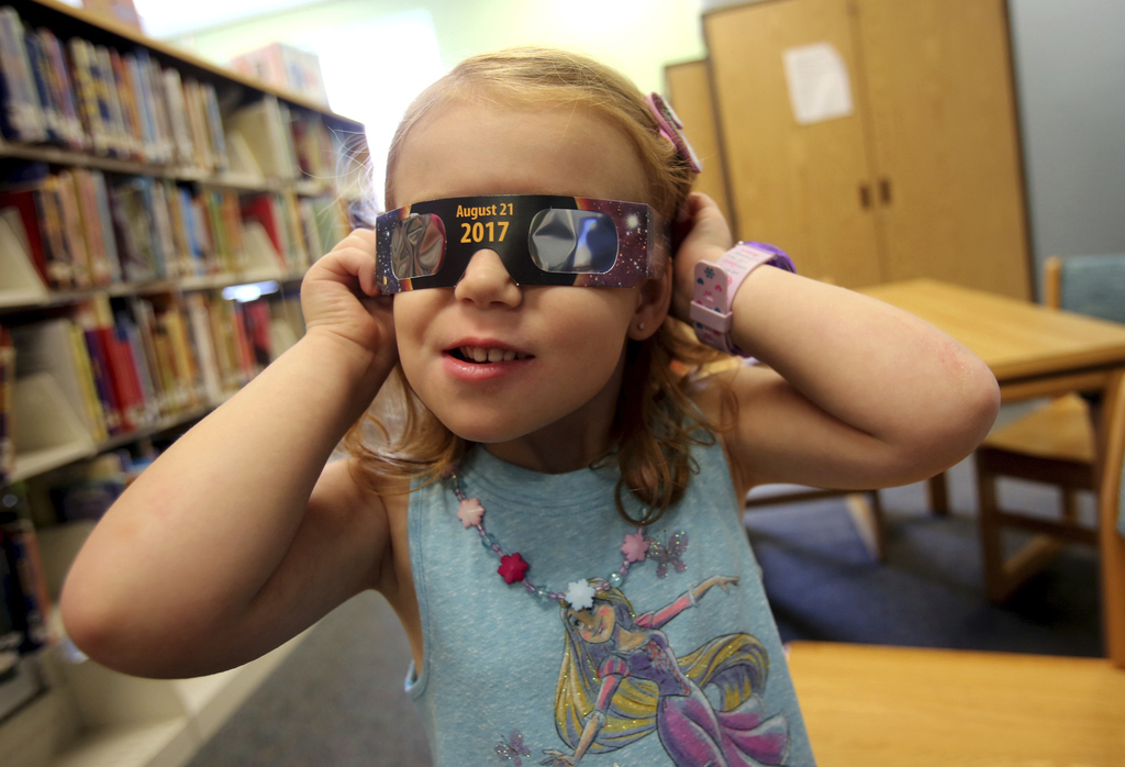FILE - In this Wednesday, Aug. 2, 2017 file photo, Emmalyn Johnson, 3, tries on her free pair of eclipse glasses at Mauney Memorial Library in Kings M...
