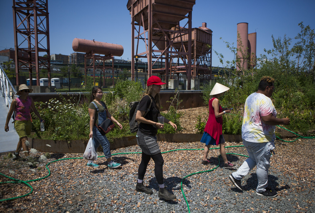 In this Aug. 1, 2017, photo, volunteers and crew arrive on the Swale in New York. The Swale garden is an old construction barge planted with vegetable...