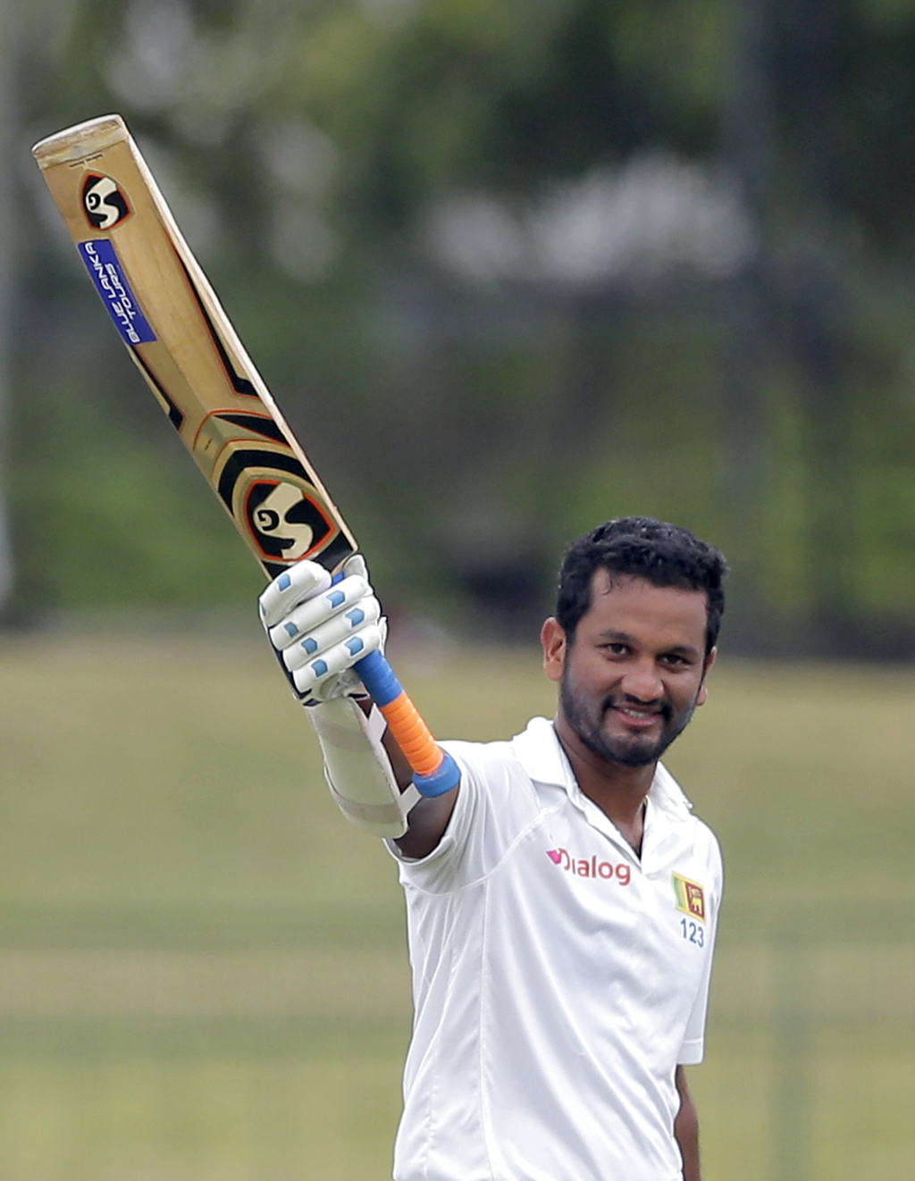 Sri Lanka's Dimuth Karunaratne raises his bat to celebrate scoring a century during their fourth day's play of second cricket test match against India...