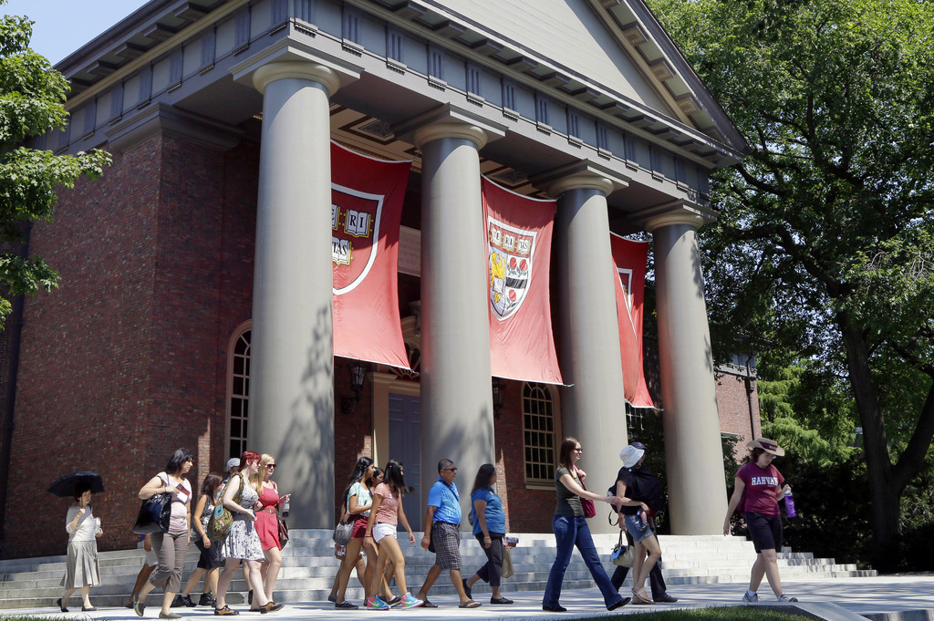 FILE - In this Aug. 30, 2012, file photo, a tour group walks through the campus of Harvard University in Cambridge, Mass. Word of an August 2017 Justi...