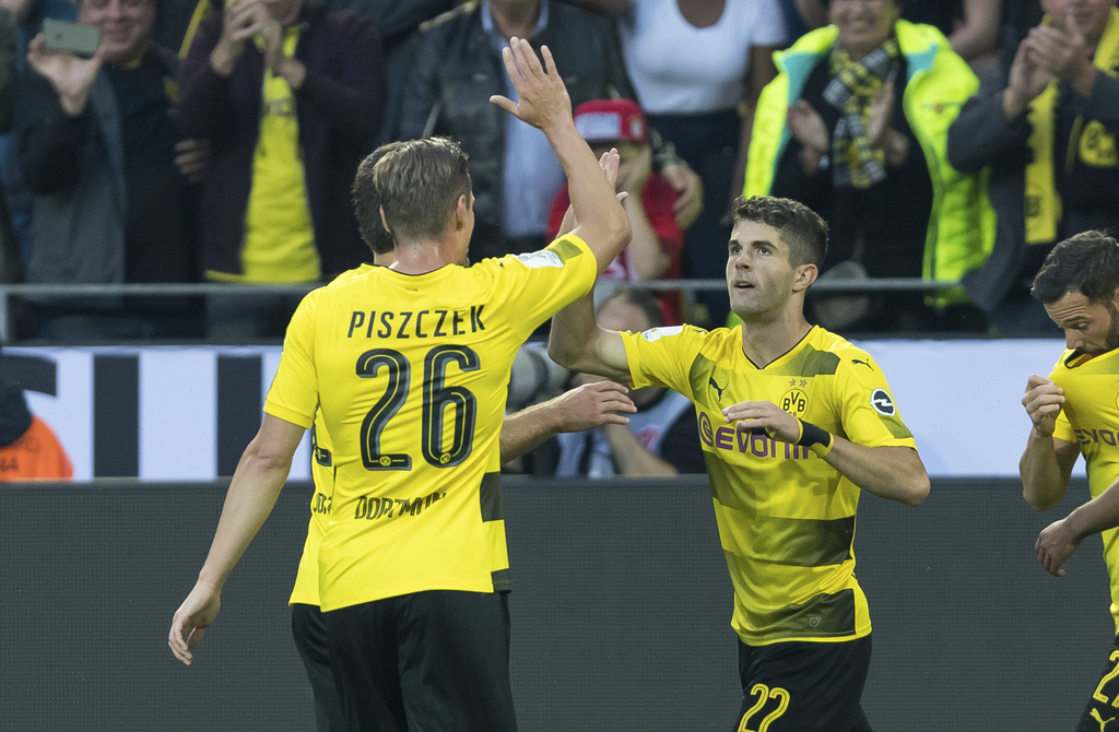 Dortmund's Christian Pulisic, second right, celebrates with teammate Lukasz Piszczek after scoring during the Supercup soccer final between FC Bayern ...
