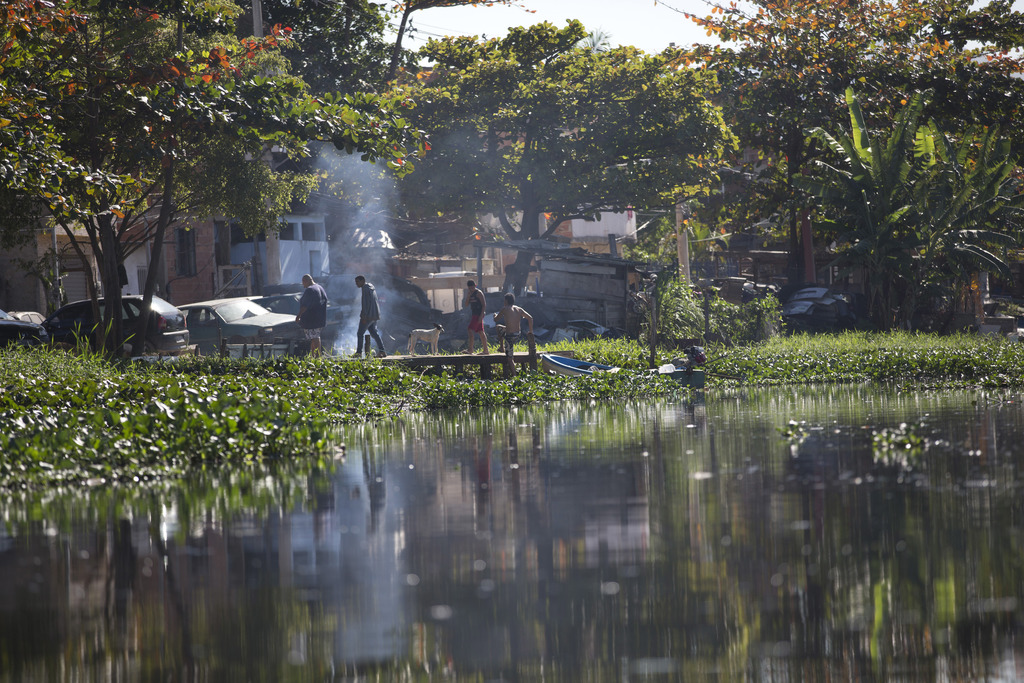 In tis July 31, 2017 photo, residents of Rio das Pedras neighborhood leave their boat moored on the polluted shore of Jacarepagua lagoon, in Rio de Ja...