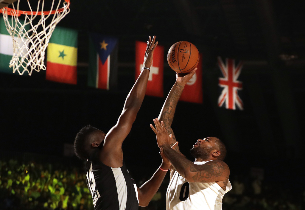 Team Africa's Luc Mbah a Moute of Houston Rockets, left, blocks a shot by Team World's DeMarcus Cousin of New Orleans Pelicans, right, during the NBA ...
