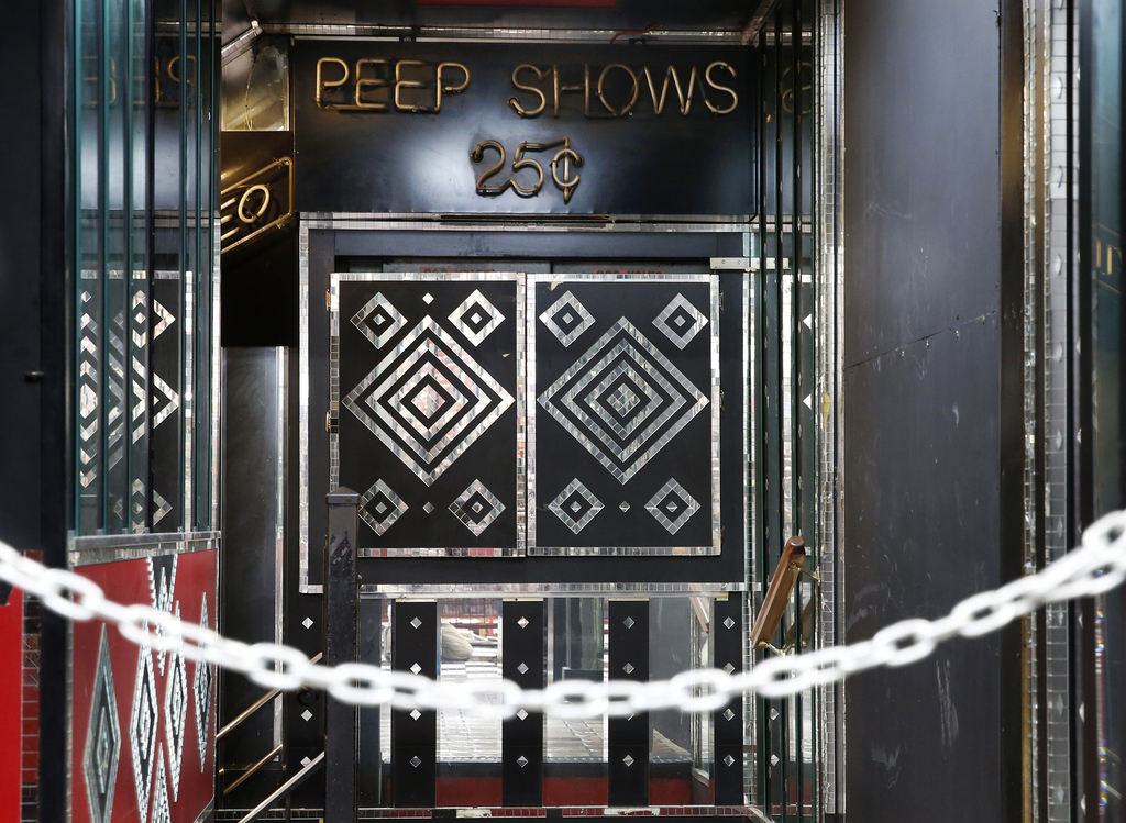 In this Aug. 3, 2017 photo, a sign advertises peep shows for 25 cents Show World Center near Times Square in New York. The city's two-decade legal war...