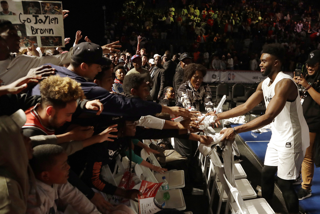 Team World's Jaylen Brown of Boston Celtics, gives away his shoes after playing the NBA Africa Game between Team Africa and Team World, at the Dome in...