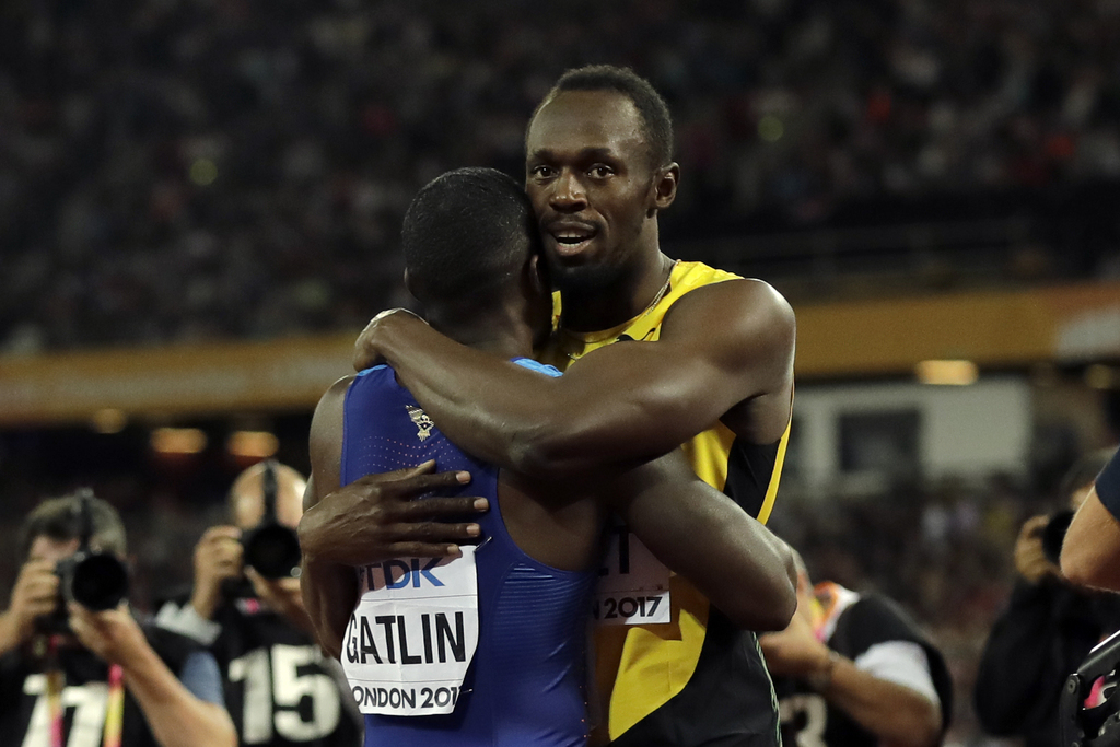Gold medalist United States' Justin Gatlin, left, and third placed Jamaica's Usain Bolt embrace each other after the Men's 100 meters final during the...