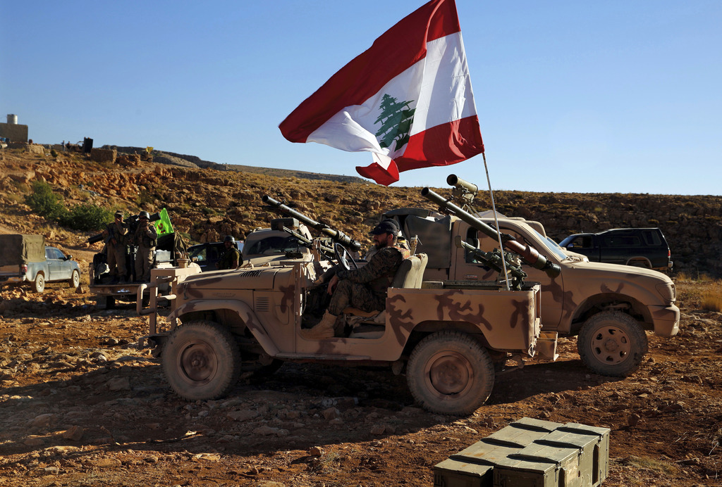 This Saturday, July 29, 2017 photo, Hezbollah fighters sit on their army vehicle at the site where clashes erupted between Hezbollah and al-Qaida-link...
