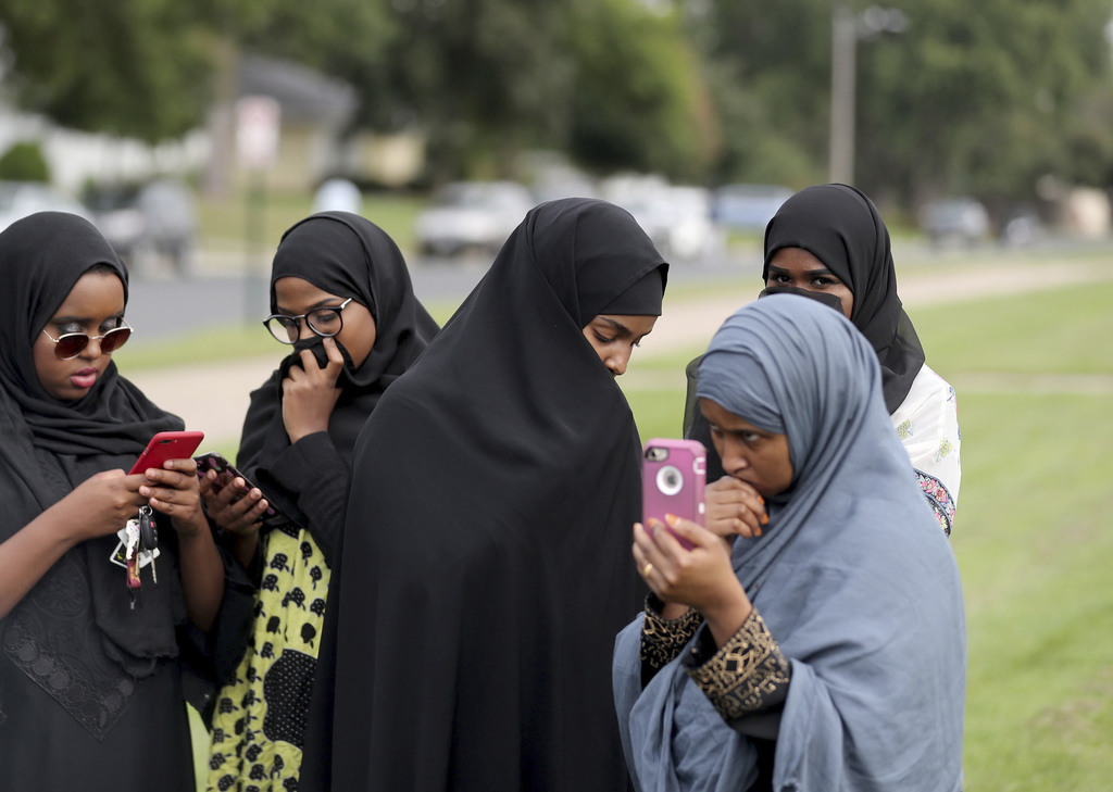 People make phone calls as law enforcement investigate an explosion at the Dar Al-Farooq Islamic Center in Bloomington, Minn., on Saturday, Aug. 5, 20...