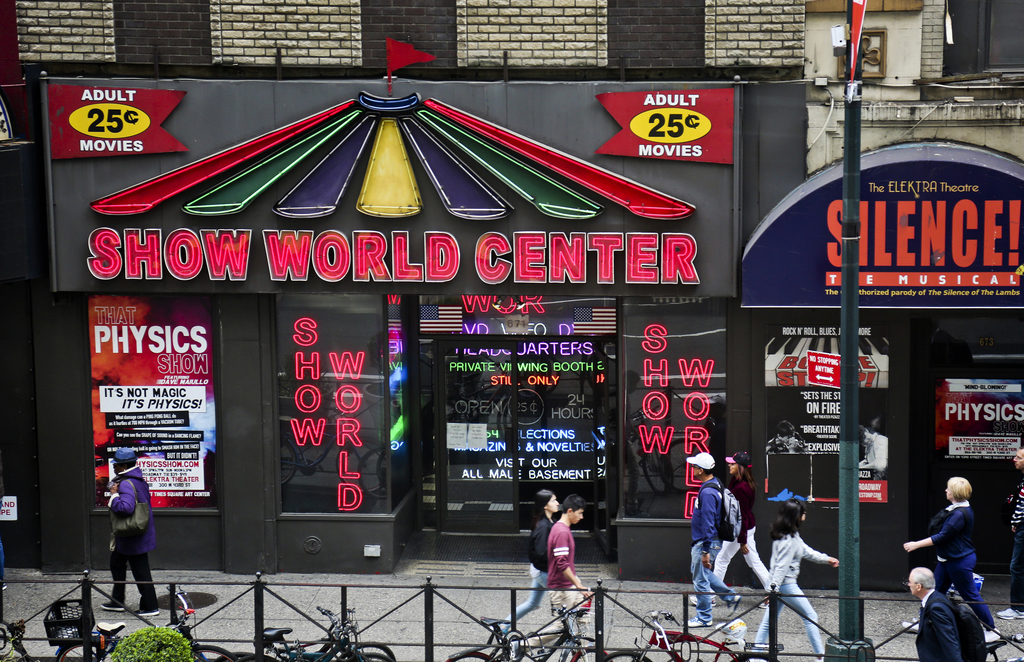 In this May 9, 2017 photo pedestrians walk by the adult store Show World Center, off 42nd Street in New York's Times Square, near the Port Authority b...