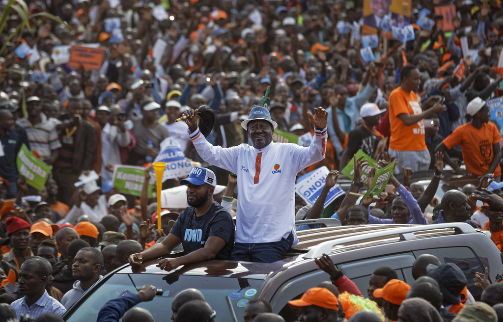 Main opposition leader Raila Odinga greets the crowd through the sunroof of his vehicle as he arrives for his final electoral campaign rally at Uhuru ...