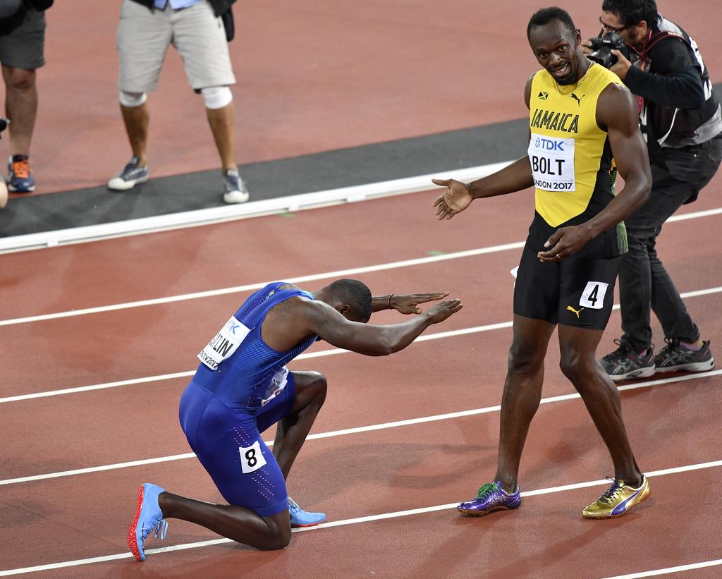 Justin Gatlin, ganador de la medalla de oro, se arrodilla frente a Usain Bolt, ganador del bronce, tras la final de los 100 metros en el Mundial de at...