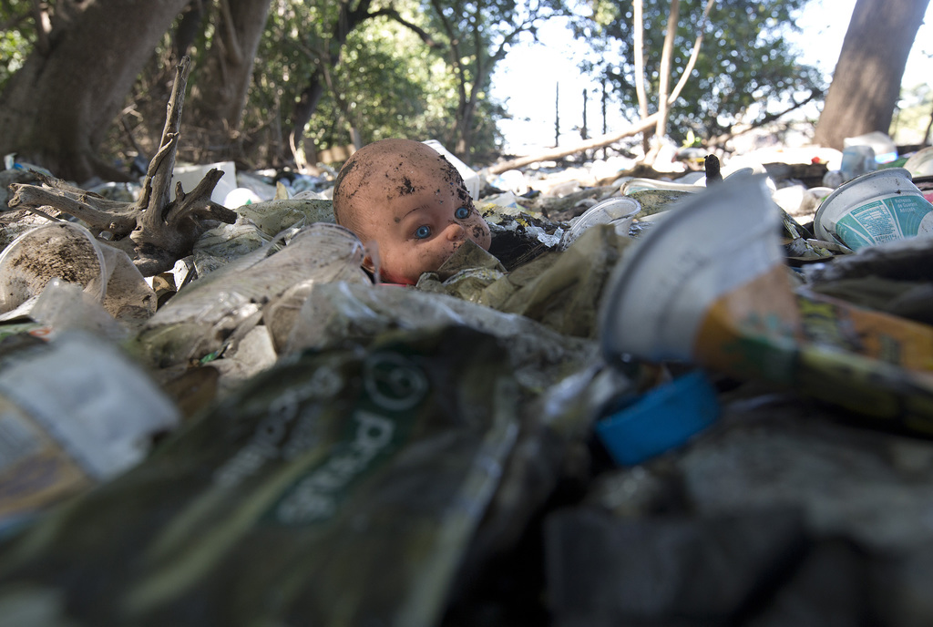 In this  July 31, 2017 photo, a discarded doll lays amid scattered garbage on the shores of Guanabara Bay, in Rio de Janeiro, Brazil. In it's Olympic ...