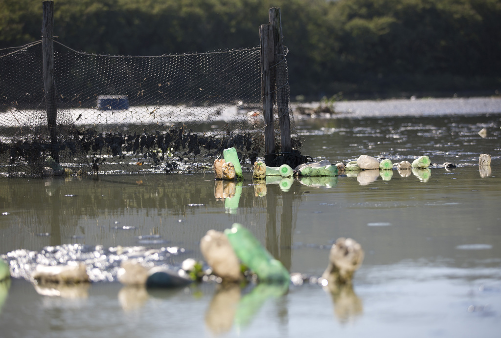 In this July 31, 2017 photo, a trash barrier hold back the surface filth of the heavily polluted Jacarepagua lagoon, in Rio de Janeiro, Brazil. Rio pl...