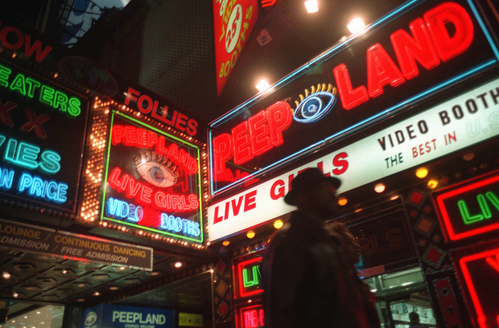 FILE - In this March 6, 1998, file photo a pedestrian walks past Peepland on Broadway in New York's Times Square, after a judge concluded the city had...