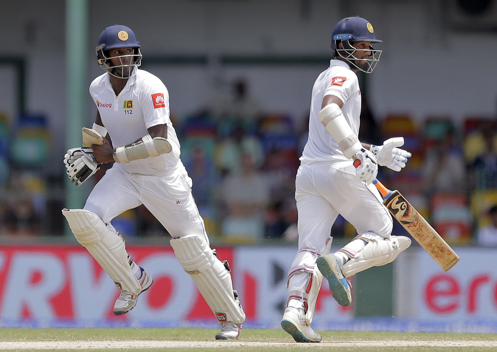 Sri Lanka's Dimuth Karunaratne, right, and Angelo Mathews run between the wickets during the fourth day's play of their second cricket test match agai...
