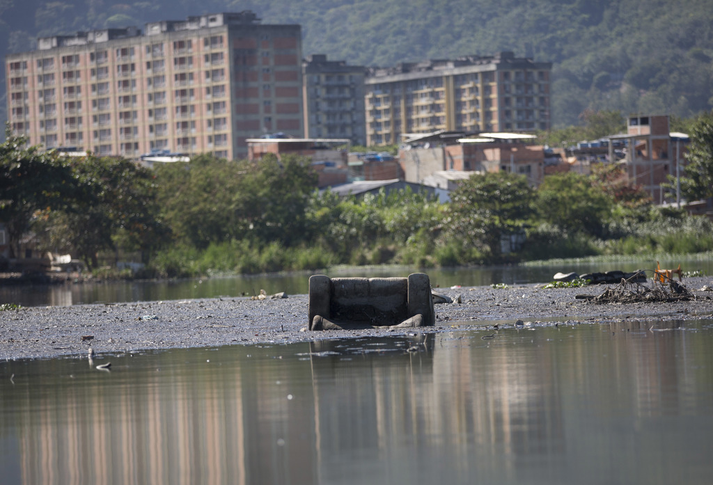 In this July 31, 2017 photo, a discarded sofa is seen in the polluted Jacarepagua lagoon, in Rio de Janeiro, Brazil. Rio pledged in its Olympic bid to...