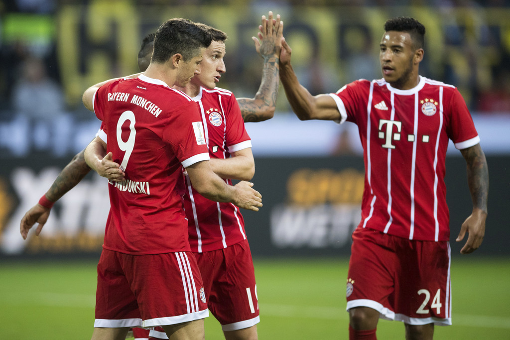 Bayern's Robert Lewandowski, left celebrates with teammates Sebastian Rudy, center, and Corentin Tolisso after scoring during the Supercup soccer fina...