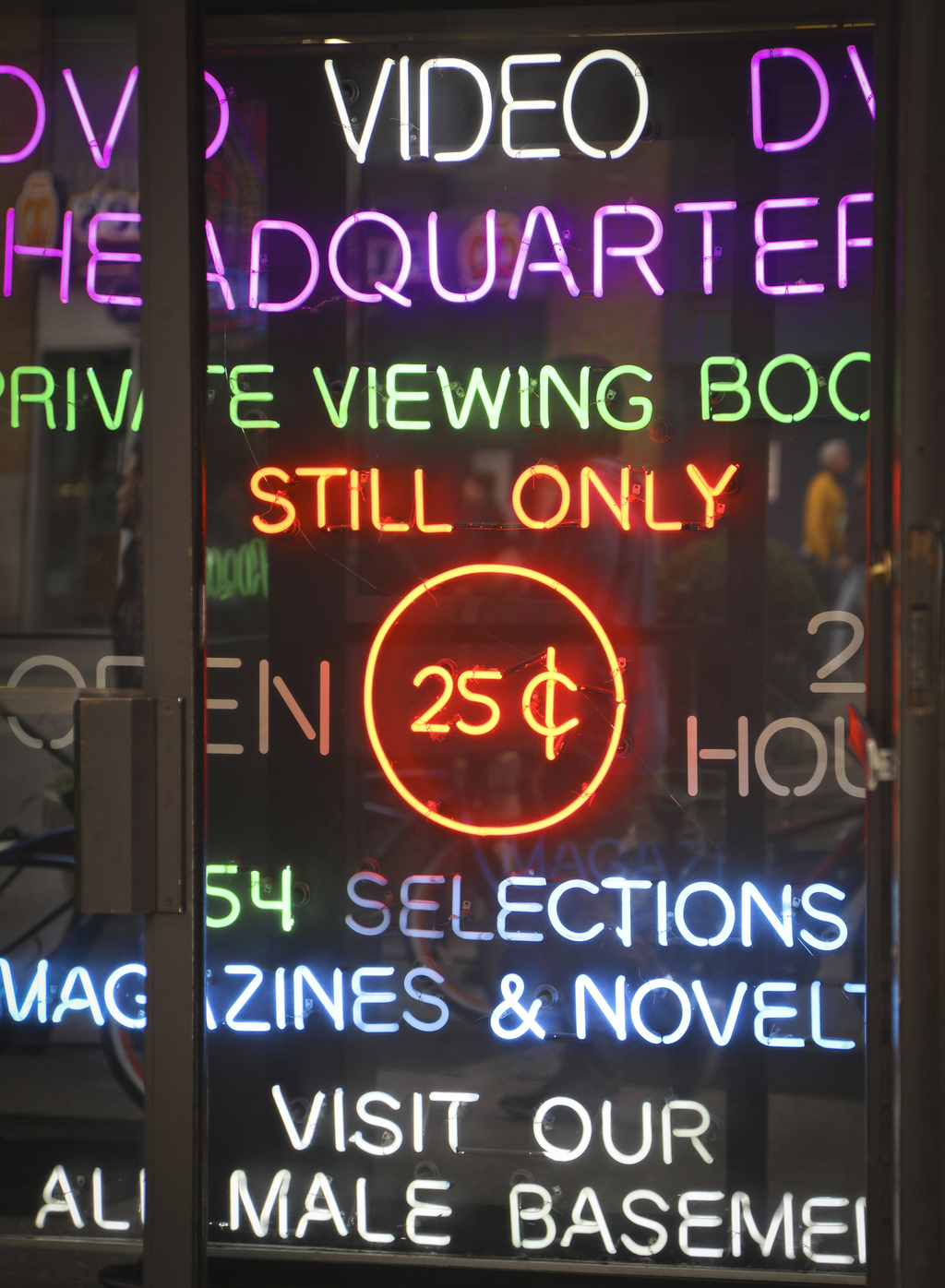 In this May 9, 2017 photo neon-lighted signs glow in the doorway of the adult store Show World Center, off 42nd Street in New York's Times Square, nea...