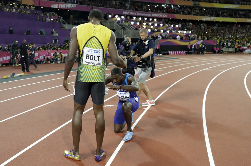 Gold medal winner United States' Justin Gatlin, centre, knees in front of Jamaica's Usain Bolt, left, who won bronze in the men's 100m final, during t...
