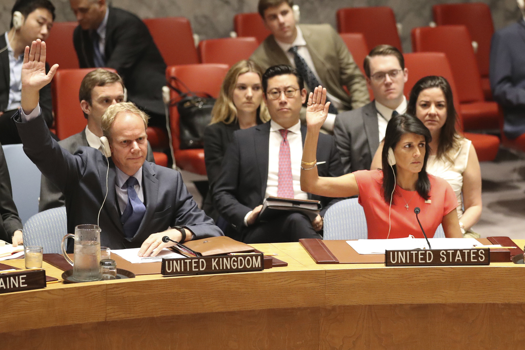 British Ambassador to the United Nations Matthew Rycroft, left, and U.S. Ambassador to the United Nations Nikki Haley vote during a Security Council m...