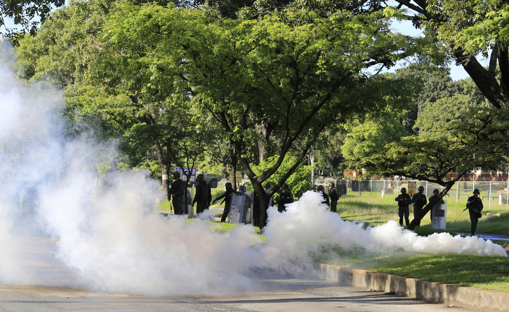 Venezuelan Bolivarian National Guard officers fire teargase towards resident that try to walks to the Military base Paramacay in Valencia, Venezuela, ...