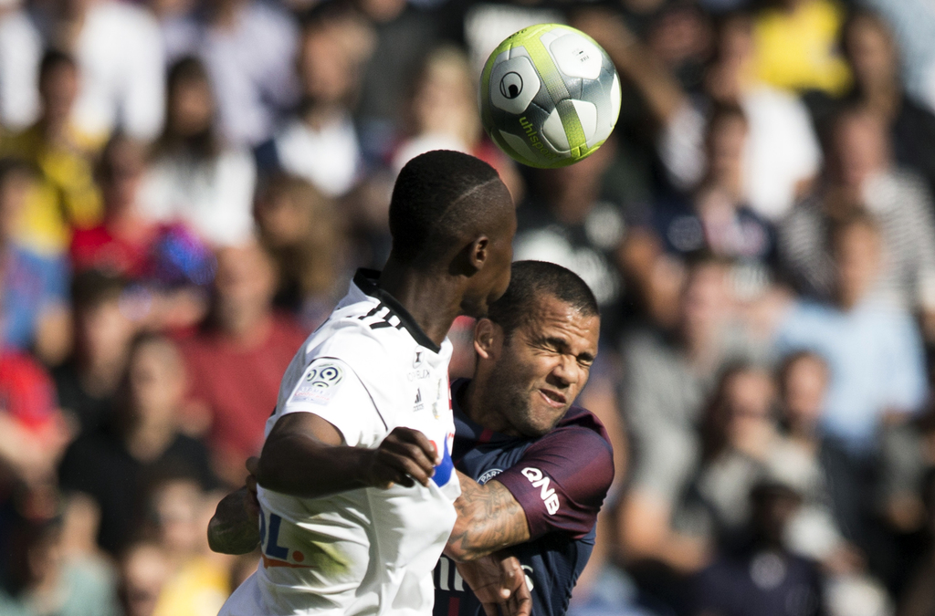 PSG's Dani Alves, right, and Amien's Khaled Adenon challenge for a header during the French League One soccer match between Paris Saint Germain and Am...
