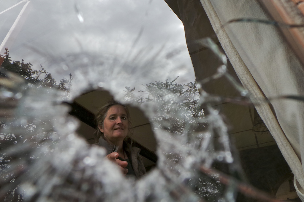 In this photo taken Wednesday, July 26, 2017, livestock breeder Maria Dodds looks through a bullet hole in a window after her home was attacked by arm...