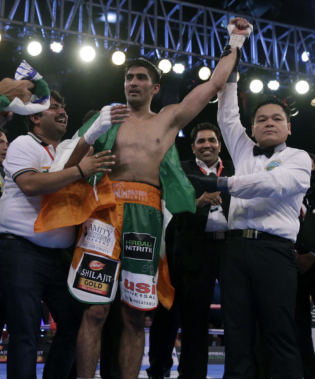 Indian boxing and WBO Asia-Pacific Super Middleweight champion Vijender Singh, centre, celebrates after winning the double title against WBO Oriental ...