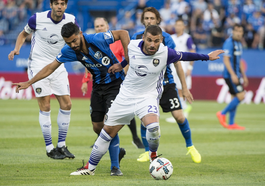 Montreal Impact defender Victor Cabrera, front left, hangs on to Orlando City midfielder Antonio Nocerino as they battle for the ball during the first...