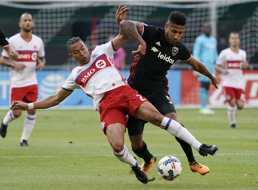 Toronto FC defender Justin Morrow (2) and D.C. United defender Sean Franklin (5) vie for control of the ball during the first half of an MLS soccer ma...