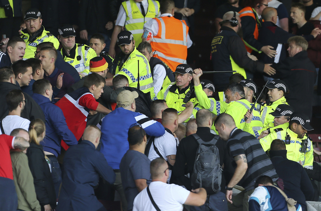 British police confront Hannover soccer club fans during the game against Burnley during their pre-season friendly match at Turf Moor, Burnley, Saturd...