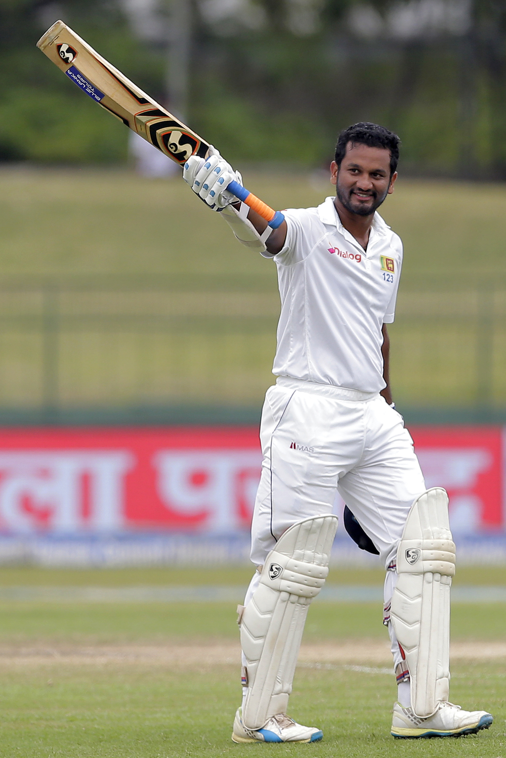 Sri Lanka's Dimuth Karunaratne raises his bat to celebrate scoring a century during the fourth day's play of their second cricket test match against I...