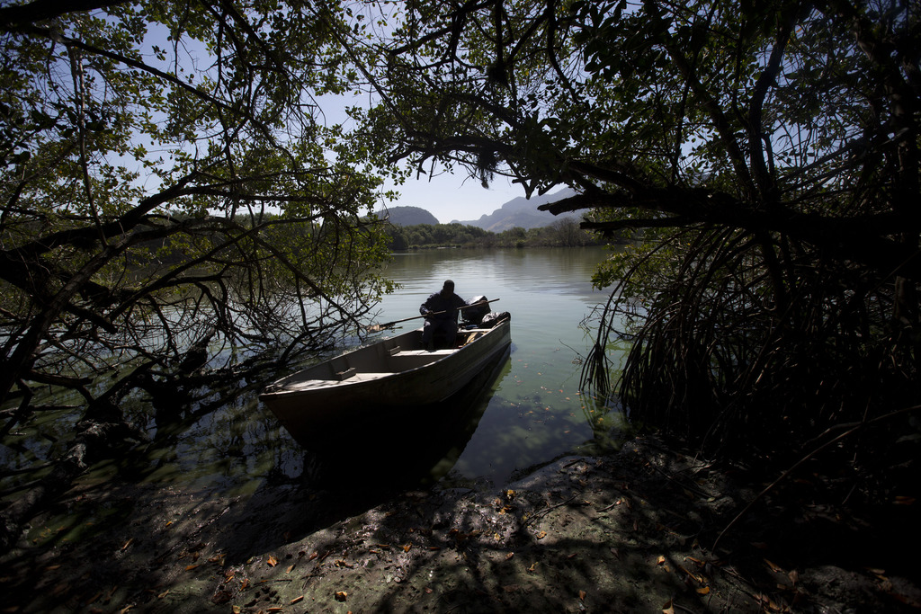 In this  July 31, 2017 photo, a man motors his boat in the polluted Jacarepagua lagoon, in Rio de Janeiro, Brazil. Rio pledged in its Olympic bid to t...