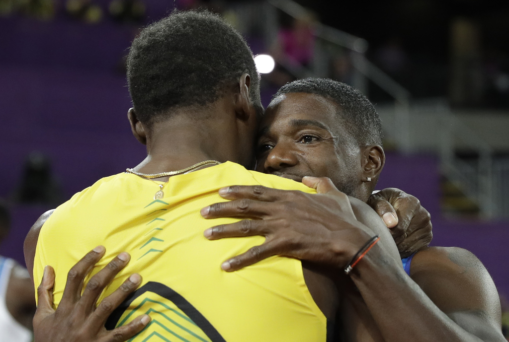 Gold medal winner United States' Justin Gatlin, right, embraces Jamaica's Usain Bolt who won bronze after the men's 100m final during the World Athlet...