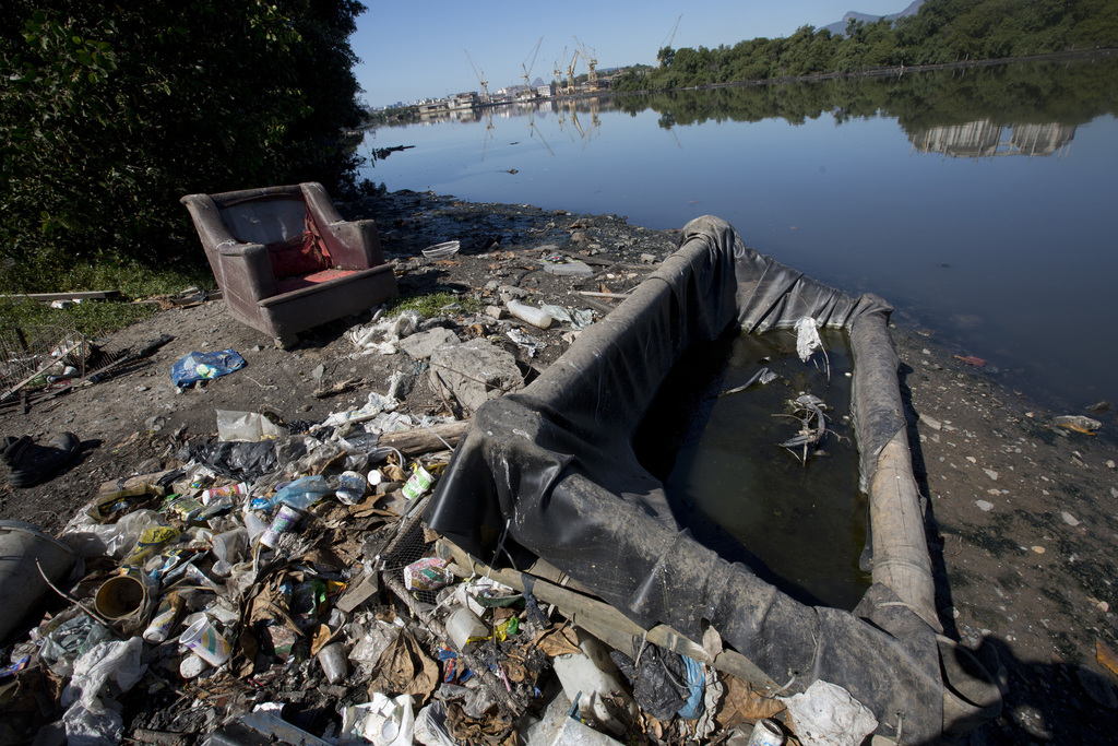 In this , July 31, 2017 photo, discarded sofas litter the shore of Guanabara bay, in Rio de Janeiro, Brazil. Rio pledged in its Olympic bid to treat 8...