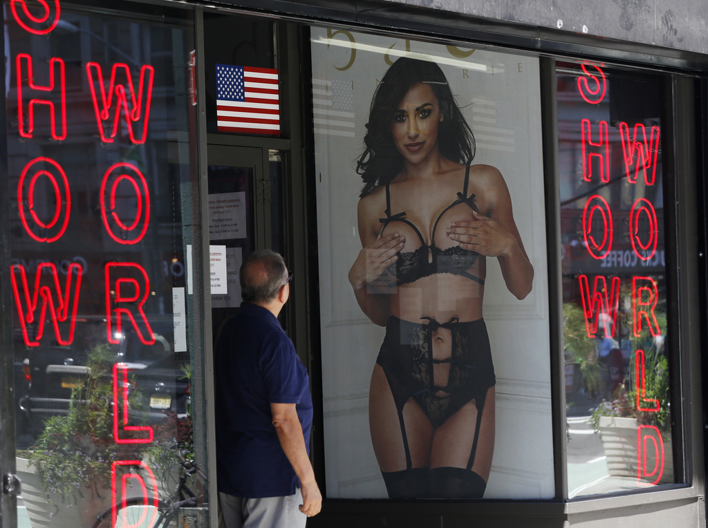 In this Thursday, Aug. 3, 2017, photo, a man looks at a poster in the window of Show World Center, one of Times Square's last surviving pornography bu...