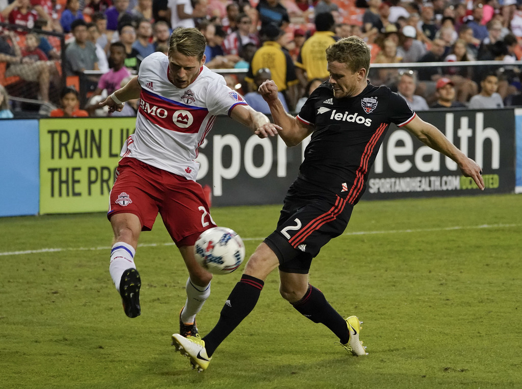 Toronto FC midfielder Nicolas Hasler (26) shoots the ball past D.C. United defender Taylor Kemp (2) during the second half of an MLS soccer match, Sat...