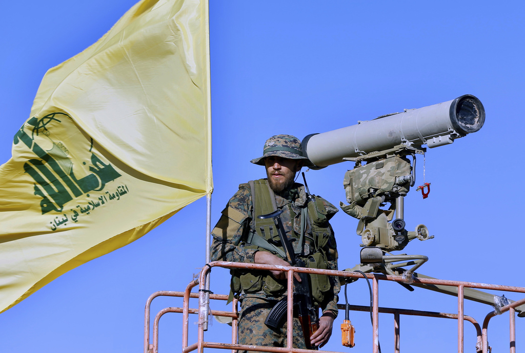 This Saturday, July 29, 2017 photo, a Hezbollah fighter stands at a watchtower at the site where clashes erupted between Hezbollah and al-Qaida-linked...