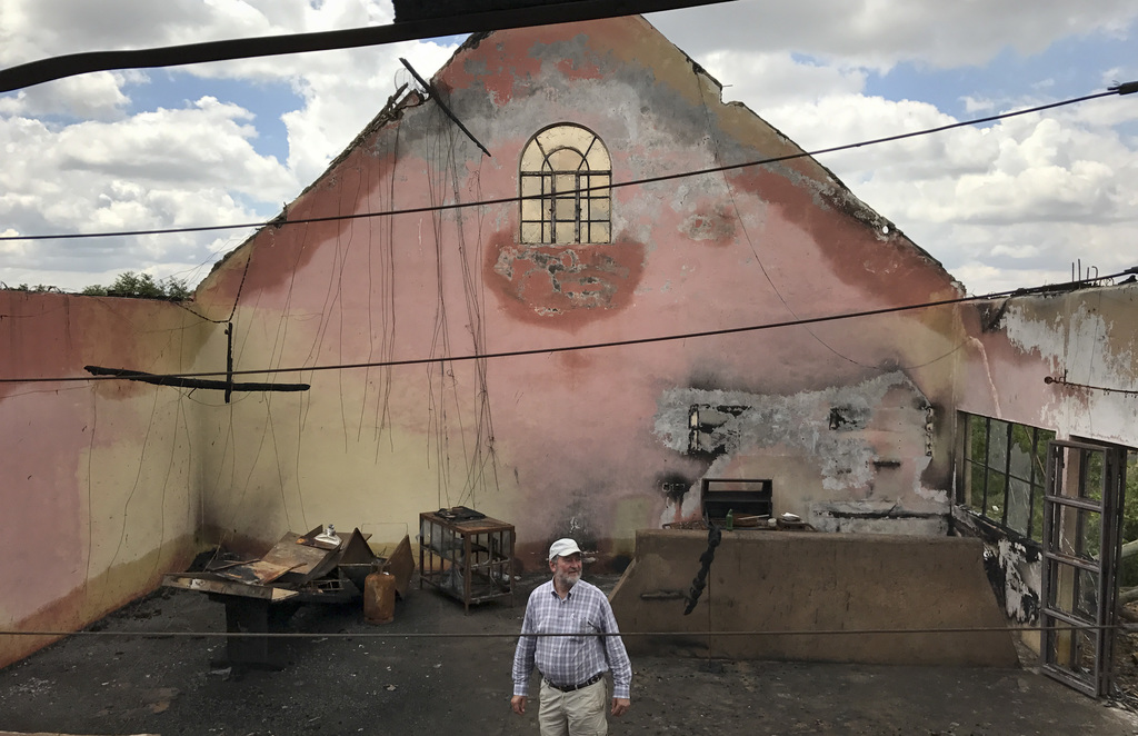 In this photo taken Thursday, July 27, 2017, farmer Martin Evans inspects a blackened home, burned down during an invasion by semi-nomadic herders on ...