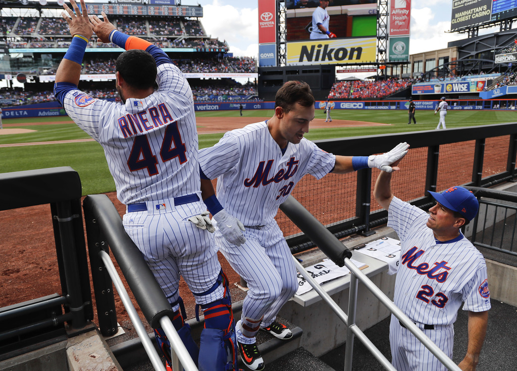 New York Mets' Michael Conforto (30) is congratulated by bench coach Dick Scott (23) and Rene Rivera (44) after hitting a solo home run against the Lo...