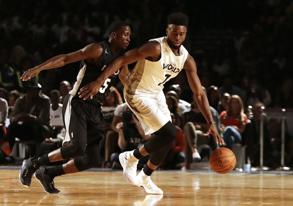 Team World's Jaylen Brown of Boston Celtics, right, drives the ball away from Team Africa's Victor Oladipo of Indiana Pacers, during the NBA Africa Ga...