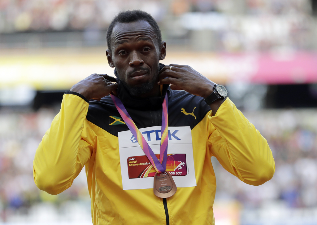 Jamaica's Usain Bolt wears the bronze during the medal ceremony for the Men's 100m during the World Athletics Championships in London Sunday, Aug. 6, ...