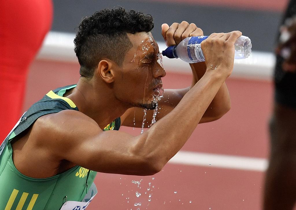 South Africa's Wayde Van Niekerk sprays water over his face following his Men's 400 meters heat during the World Athletics Championships in London Sun...