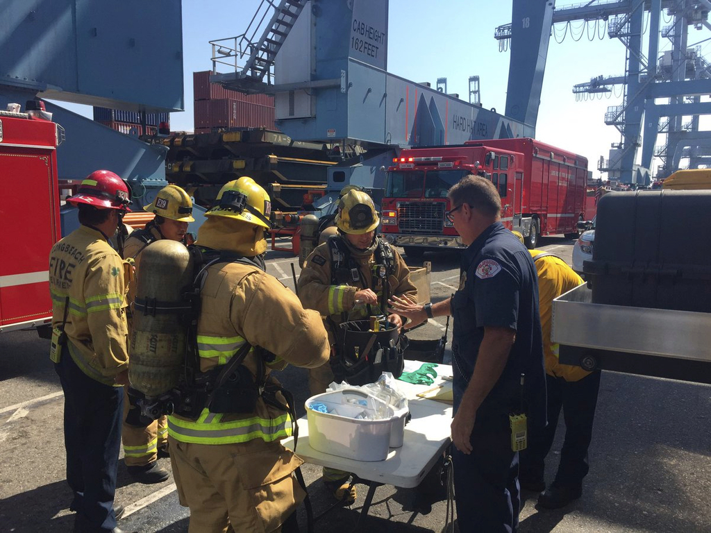 This photo courtesy of the Long Beach Fire Department shows firefighters at at Pier G, after boarding a ship in the Port of Long Beach, Calif., Sunday...