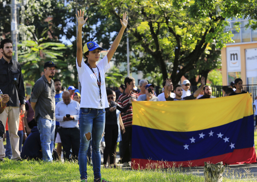 A woman raises her arms as a surrender signal to a lineup of Venezuelan Bolivarian National Guards soldiers outside of Military base Paramacay in Vale...