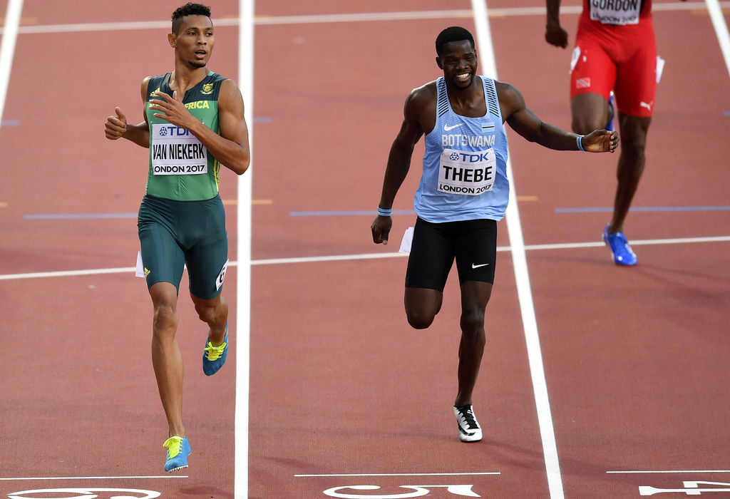 South Africa's Wayde Van Niekerk, left, leads Botswana's Baboloki Thebe to the line during their heat of the Men's 400 meters at the World Athletics C...